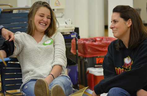 Senior Kaylin Williams laughing with leadership adviser Sarah Green to get her mind off of blood, as she donates at the school blood donation on November 14.