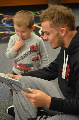 Senior Marquise Doherty shares a story with the middle child of the Marcantonio family, Jackson, on Dec. 14 in the Winnetonka media center.