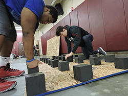 Senior Cody Carter and freshman Clayton Camacho apply pressure to adhere the foam blocks to the plywood on Dec. 23 in the wrestling room.