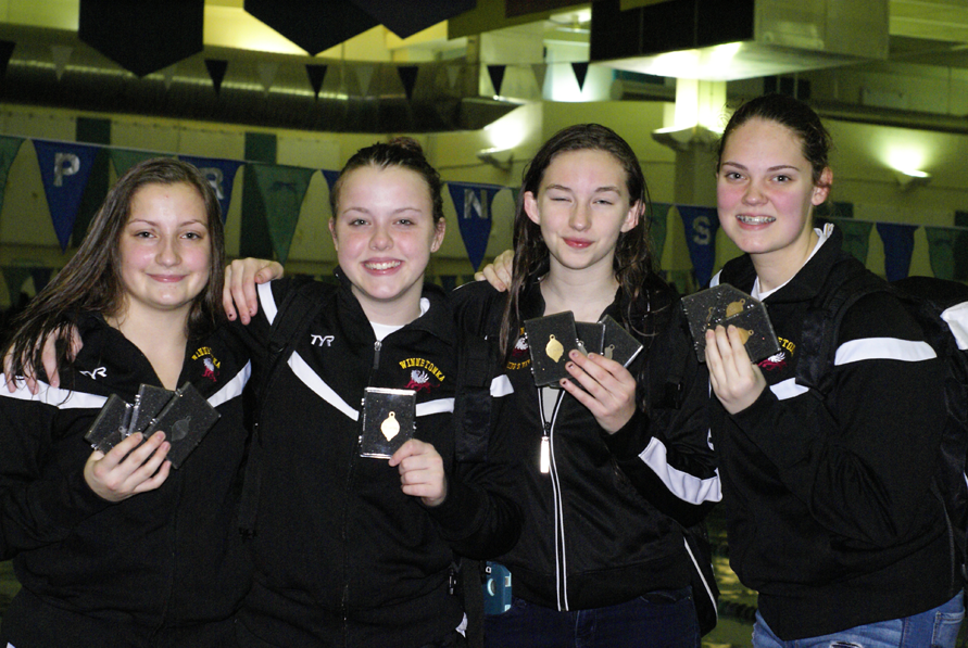 Junior Suzanna Zimmerman, (left) freshmen Emily Reed, Kathryn Bullock and Anna Braman posing with their medals after the JV conference swim meet on Jan. 28.
