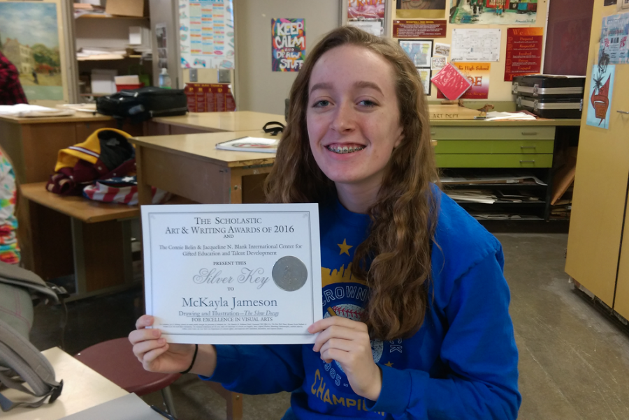 Junior Mckayla Jameson holding the Silver Key award from the Scholastic Art Competition that she earned.