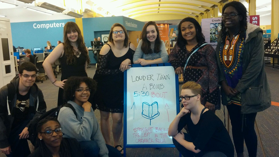 Sophomore Danielle Dodd, juniors Vincent Costanza, Sally Dishman, Kiara DeVine, Susan Engstrom, Tashayona Gulley, Lillian Juma, Alyssa Magrone and senior Mikayla Marcel posing with sign at LTAB competition.