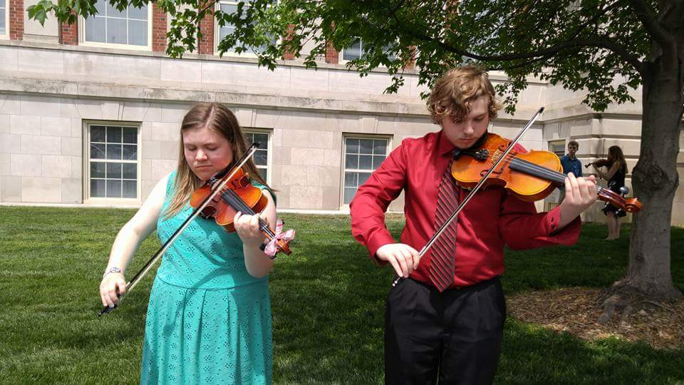Senior Brooke Glaszczak and junior Riley Davison warming up for their violin duet at state contest on April 28.