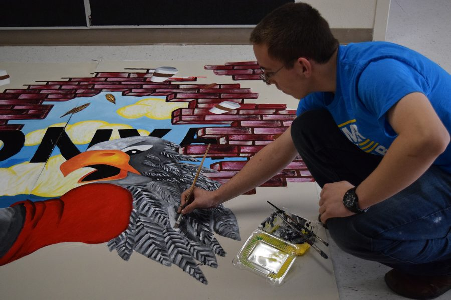 Junior Matthew DeHass painting on the mural for Griffin Grounds on Nov. 9.