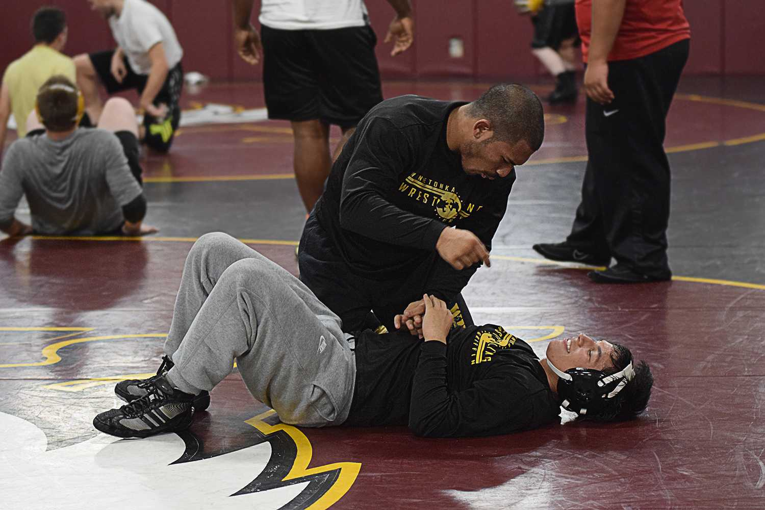 Senior Michael Aquino gives some advice to his younger brother, freshman Jordan Aquino during practice after being able to overpower Jordan in a short amount of time.