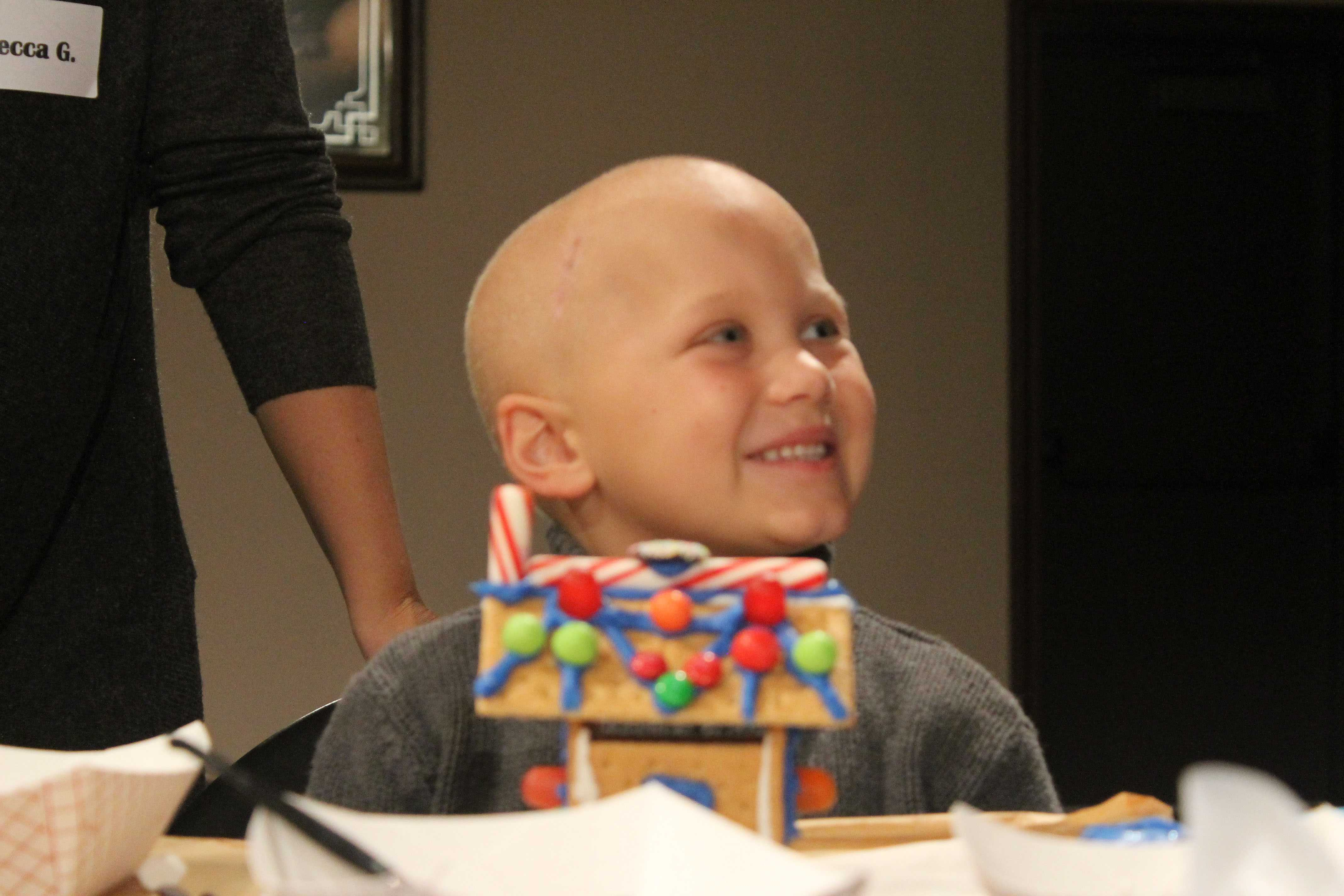 One of the children with cancer builds a gingerbread house with the orchestra students on Dec. 11.