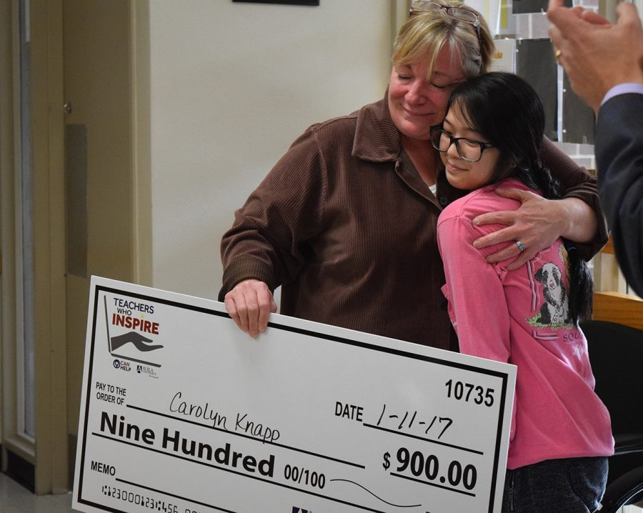 Science teacher Carolyn Knapp receiving a $900 award for being one of the inspiring teachers selected by KMBC 9 while embracing and senior Lan-Nhi Tran who nominated Knapp.