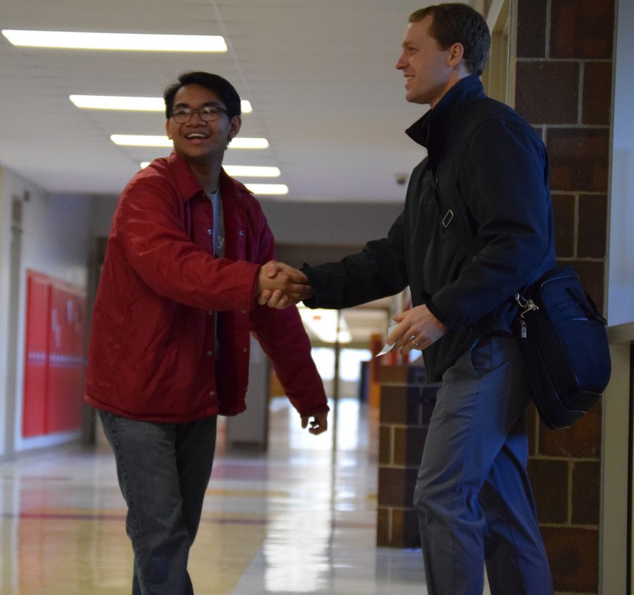 Senior Eldridge Villegas shakes hands with one of the visitors.
