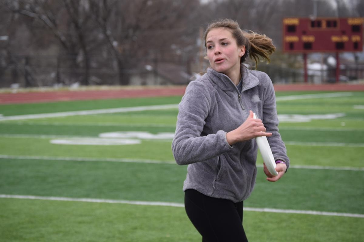 Senior Cayla Adamson spins around while holding the frisbee in order to throw it to another teammate.