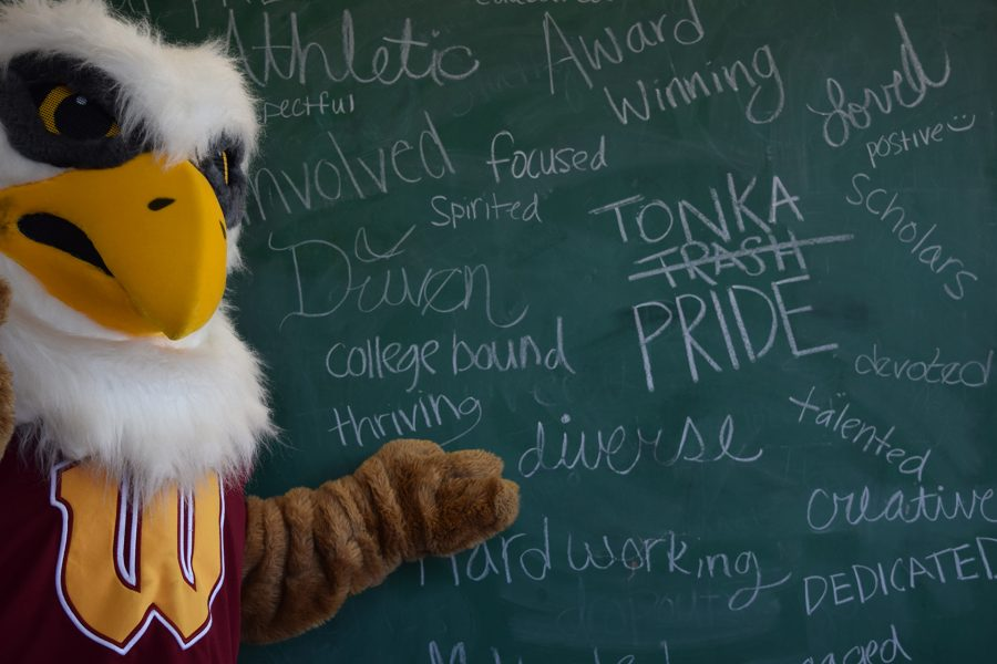 The Griffin mascot stands in front of a chalkboard where negative were erased and replaced with words that students and staff members feel describe Tonka.