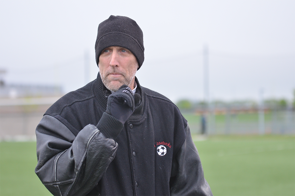 Head soccer coach David Flynn closely observes his players during a game.