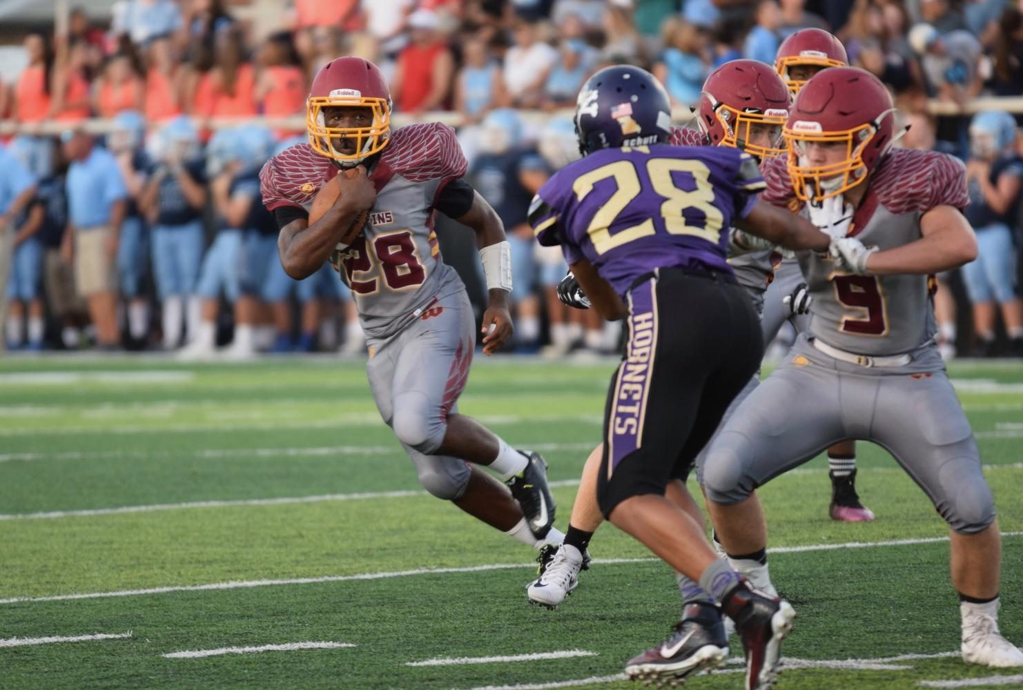 Sophomore Dre'Maine Fanning from Tonka faces off against number 28 from Northtown as he tries to avoid being blocked while running with the ball.