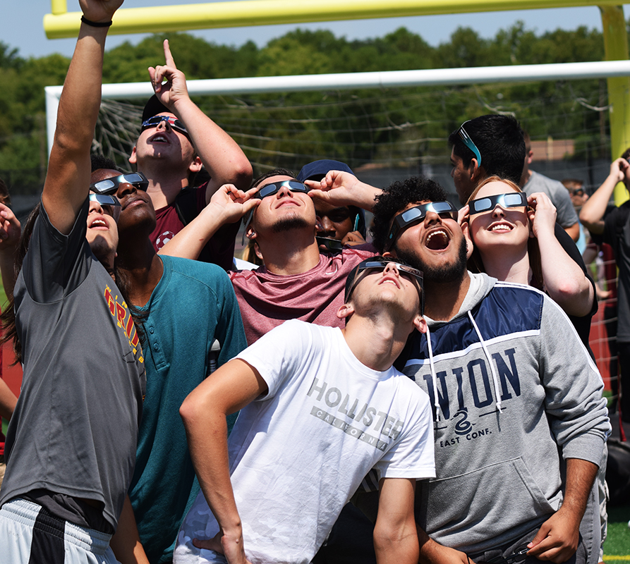 A group of students look up at the sun as the moon begins to pass in front of it.
