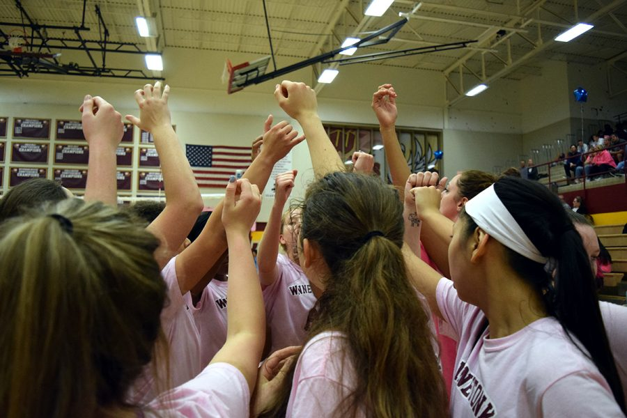 """After gaining four consecutive points against Oak Park during their first set, the team emerges from a timeout while cheering """"Tonka""""."""