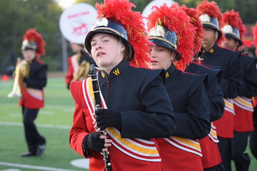 Junior Bella Middaugh marches with the PRIDE band while playing clarinet at the Sept. 29 homecoming football game before the first quarter. Middaugh was selected as the 11th chair clarinet for the Kansas City Metro All-District Band.