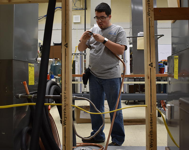 Senior Payton Stephenson works on a part for a heating and cooling system on Dec. 7 at the Northland Career Center in the Heating, Ventilation, Air Conditioning, and Refigeration class.