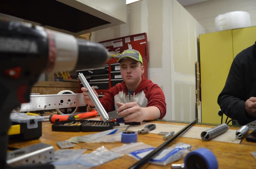 """Junior Brandon Burt contemplates design options at a Saturday build day on Jan. 20. """"I think we all just have a passion for engineering and design. It's fun to start from nothing and to end up with something that you made from scratch,"""