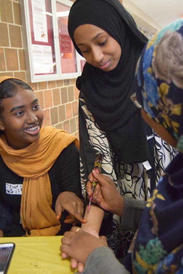Freshman Roda Jama discusses with sophomore Ruweyda Hassan, while Hassan prepares to put a henna on freshman Sumaiya Mohamud's wrist.