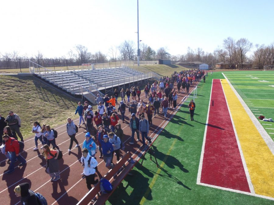 An estimated 500 to 600 students march on the track after walking out of their second block classes in order to advocate for school safety and fight against gun violence.