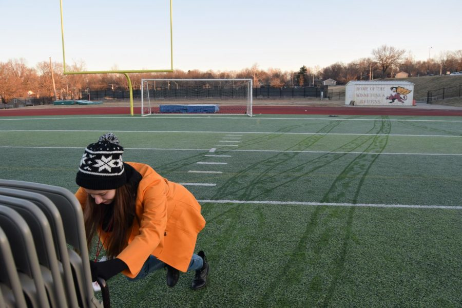 Junior+Makayla+Cambiano+pushes+a+rack+of+chairs+onto+the+football+field+covered+in+frost.+Cambiano+is+a+member+of+seven+stagecraft+students+who+helped+juniors+Joe+Bell+and+Katie+Bullock+and+senior+Danielle+Dodd+set+up+for+the+event.+