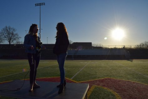 Senior Danielle Dodd and junior Katie Bullock discuss plans for the walkout on the stage set up on the football field.