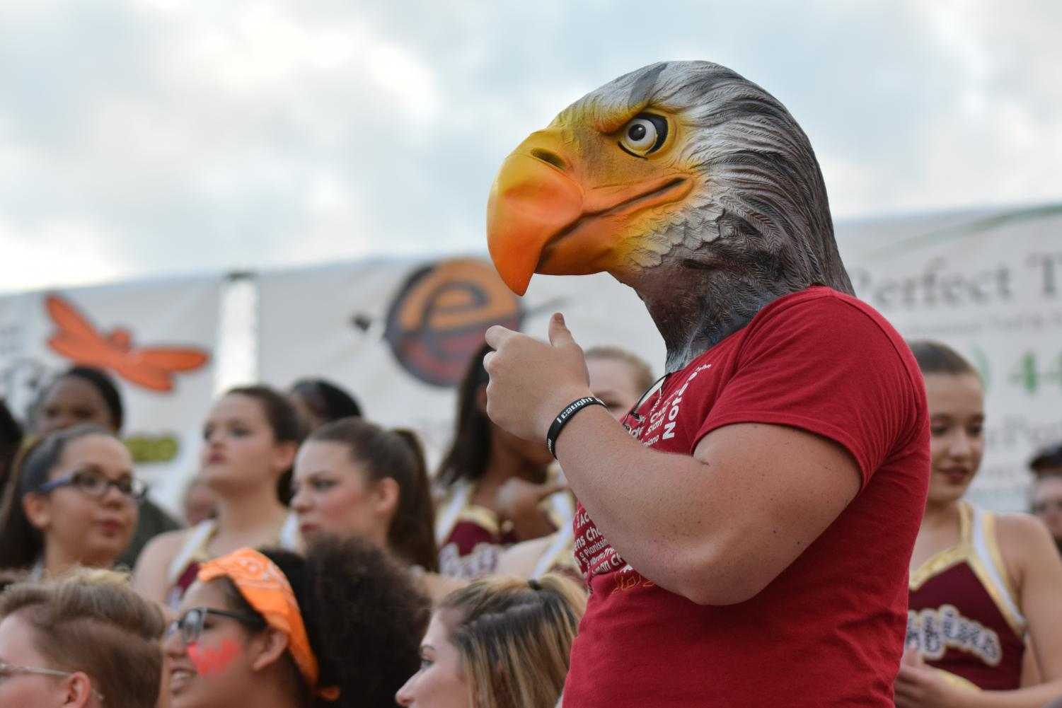 Senior Jackson Mattingly wears a plastic griffin's mask as he stands on the senior wall at the Aug. 18 varsity football game against Park Hill South at the North Kansas City District Stadium.