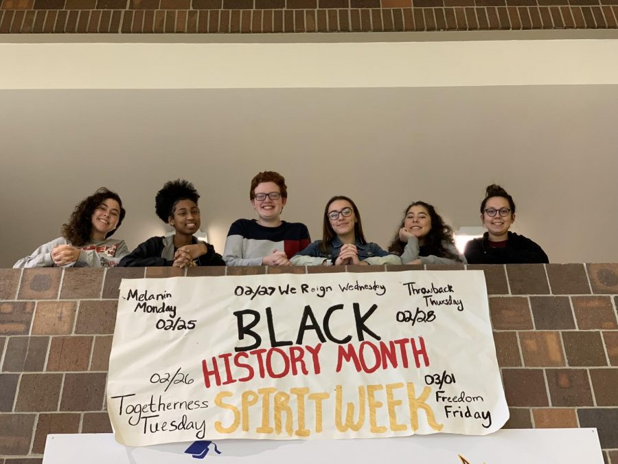 From left to right: Junior Ashtin Holman, junior Justice Thompson, senior Trenton Kauzlarich, senior Madison Mayes, junior Aris Holman and junior Jaelee Pittel pose above the Black History Month sign RISE painted. The sign, intended to bring more awareness to the upcoming spirit week, was hung above the main entrance corridor to grab the attention of students walking in the building. Photo by Derek Walsh.