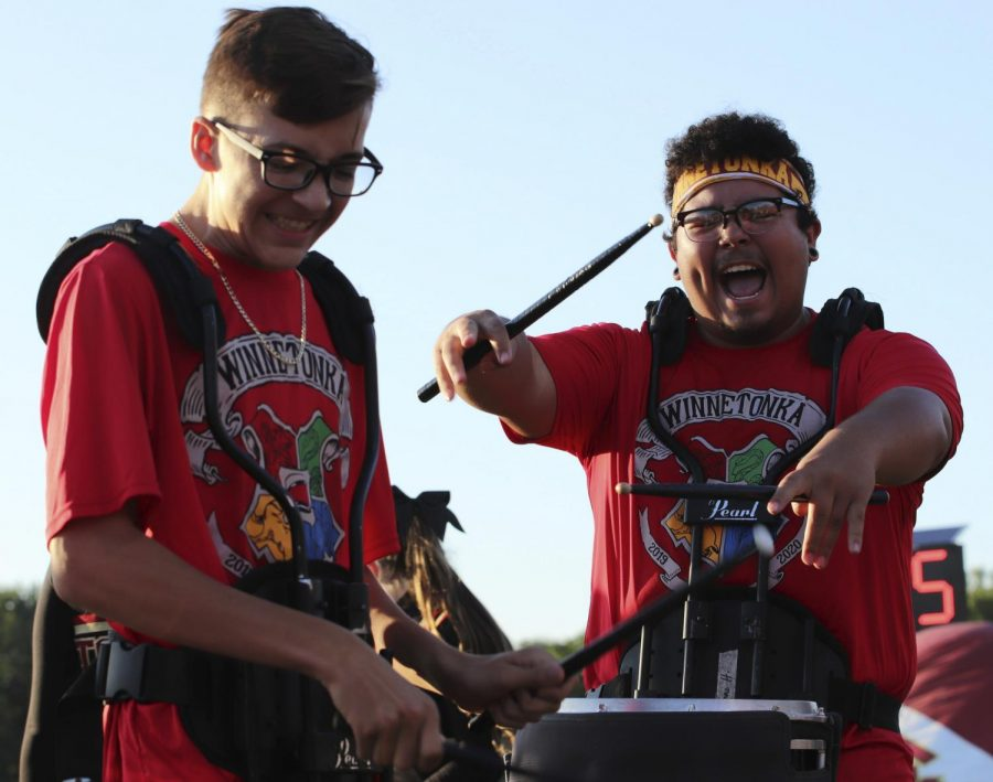 Senior Isaac Hernandez hypes up junior Alex Kisler during the drum line performance of Jig 2 at the first Friday Night Lights game on the Winnetonka football field on Aug. 30. Photo by Kelsey Cowden.