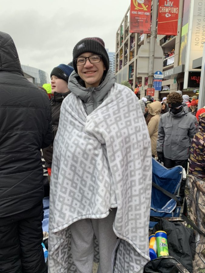 Junior Alex Kisler keeps himself warm before seeing the parade on alongside the streets of Kansas City on Feb. 5. Submitted photo.