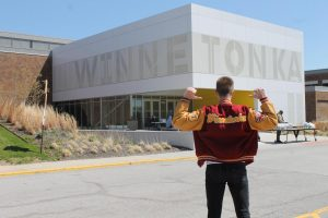 Aksels proudly stands in front of Winnetonka after the building is closed due to a stay-at-home order. In the background, staff members work hard to prepare food packages for the families they serve. This is his